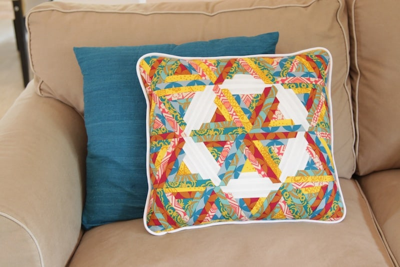 Triangle log cabin blocks form a circular design. By Bonjour Quilts