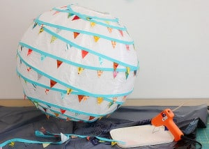 Simply glue the bunting along the paper lantern frame with a glue gun