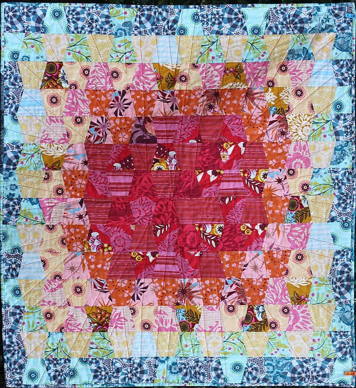 An easy baby quilt made from tumbler blocks in Anna Maria Horner fabrics - by Bonjour Quilts