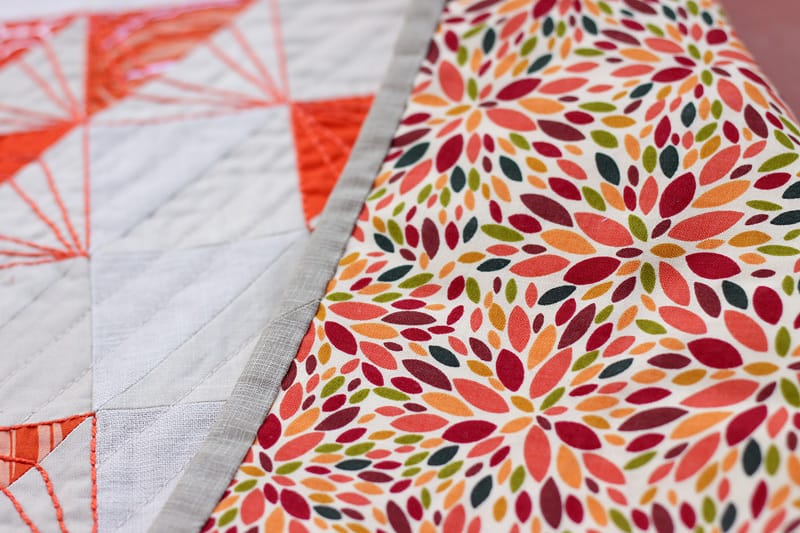 Modern quilted table runner made with HSTs - orange and tan with embroidery