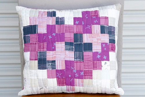 A handmade heart shaped quilted patchwork cushion by Kirsty at Bonjour Quilts