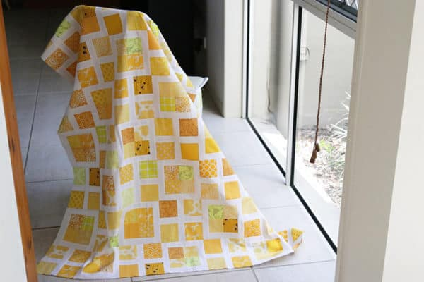 Scrappy yellow quilt made with squares