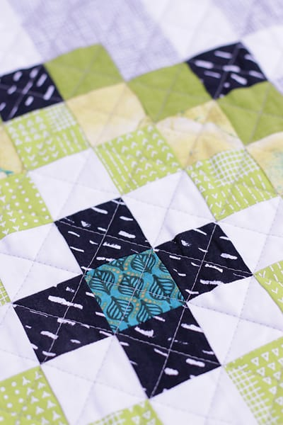 A close up of the cross hatch quilting used on a Scrap Magnet patchwork quilt.