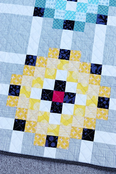 A close up of a patchwork quilt block in a Scrap Magnet throw size quilt.