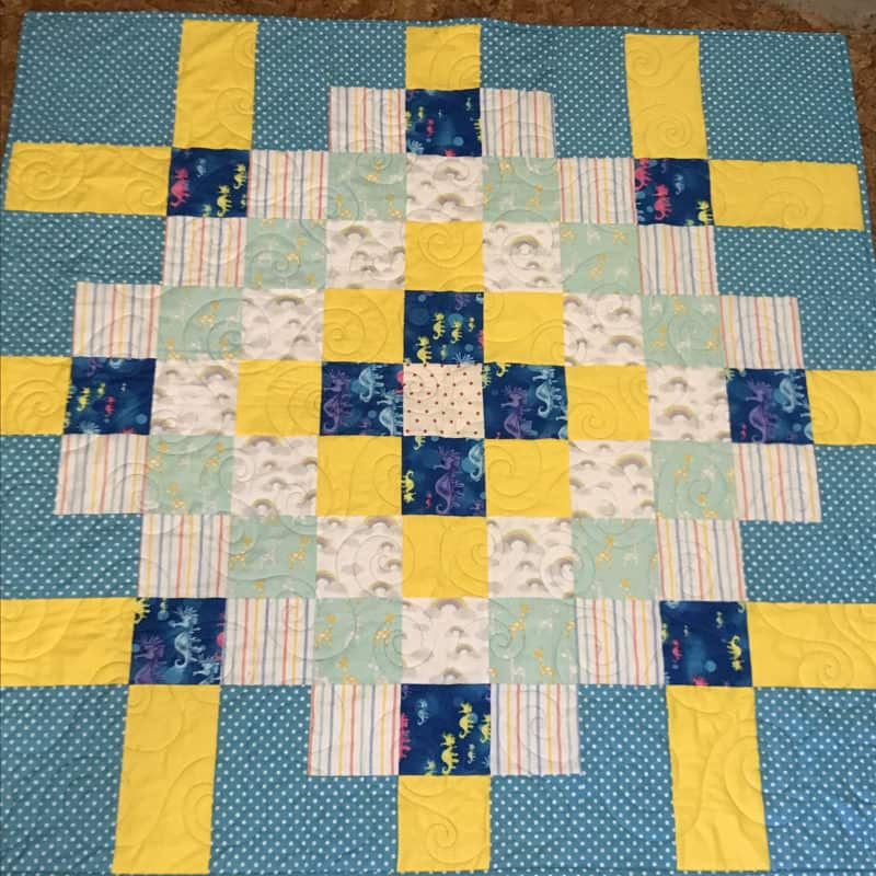 A scrappy patchwork baby mat sewn in bright colours