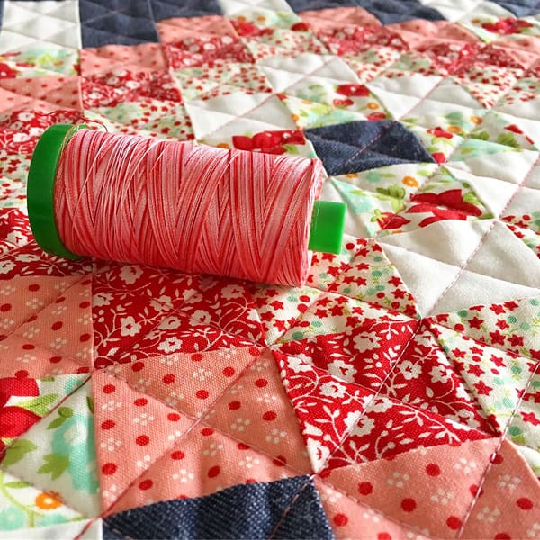 A scrappy patchwork quilt block with a spool of variegated thread.