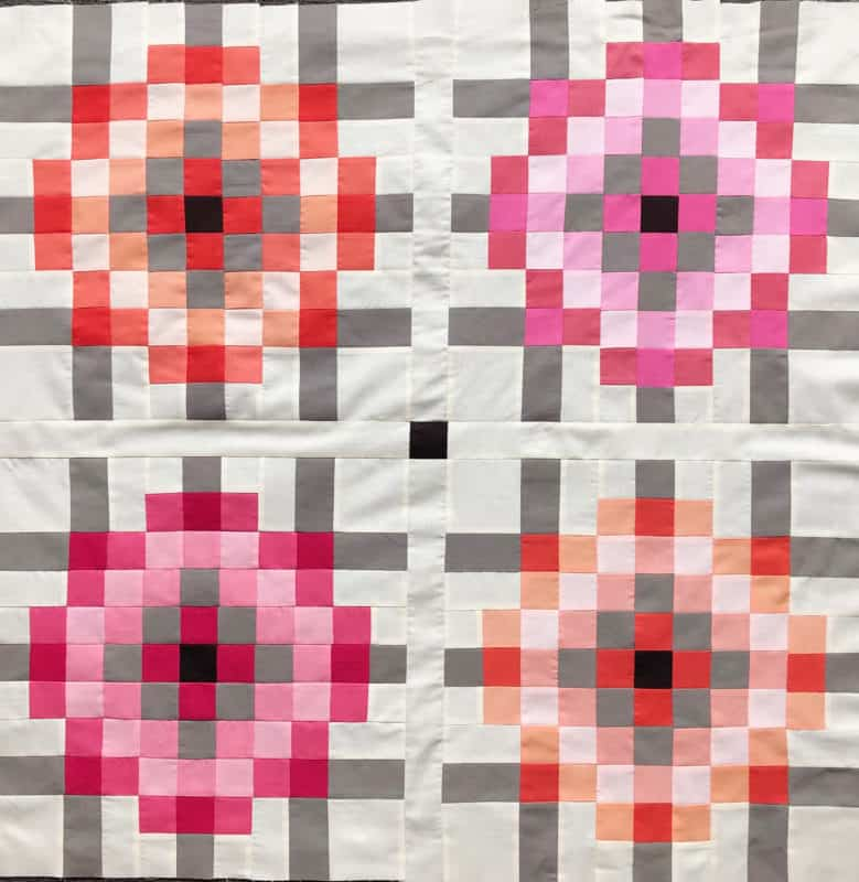 A scrappy baby quilt made in peach and pink tone fabrics. Sewn by Suz, one of the Scrap Magnet testers.