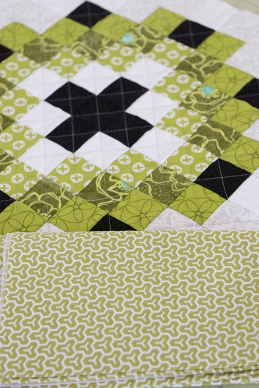 Green fabric backing for a Christmas cushion made with the Scrap Magnet  quilt pattern.