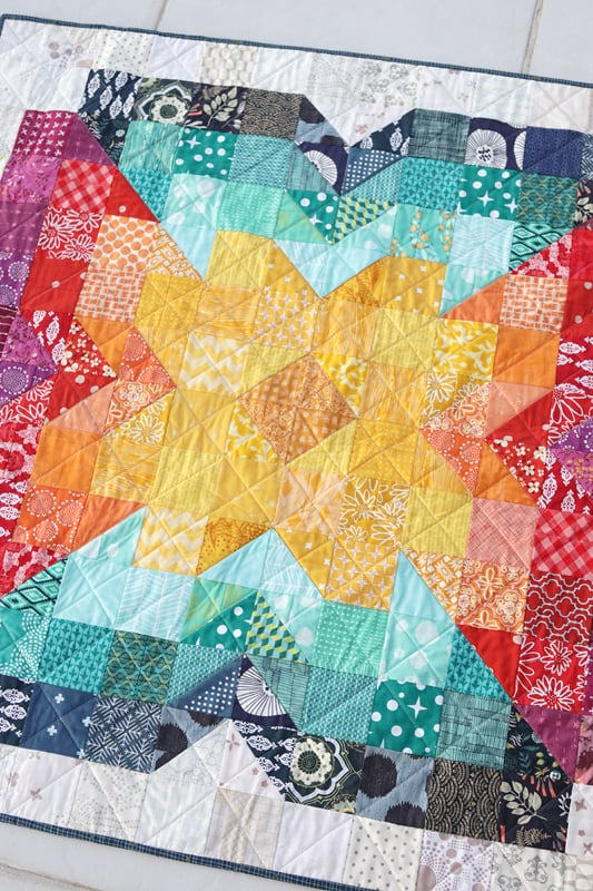 Scrappy Posie - an easy, free baby quilt pattern by Bonjour Quilts. Sew a scrappy rainbow baby quilt today with this free PDF baby quilt pattern download.