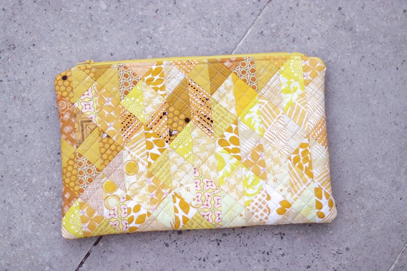 A scrappy patchwork zipper pouch in yellow.