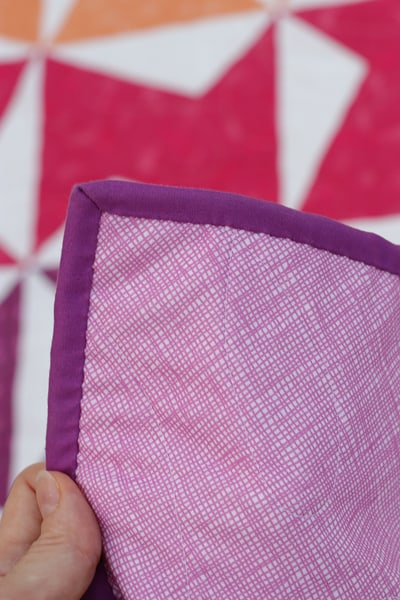 Purple binding and backing on a quilt