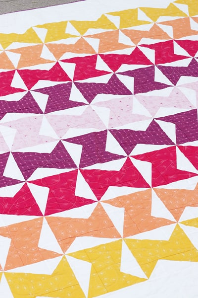 Colourful twin size quilt made with half rectangle triangle blocks