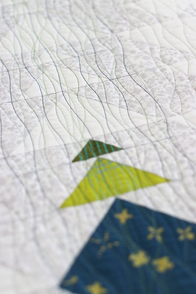 Coloured thread quilting on a flying geese quilt pattern