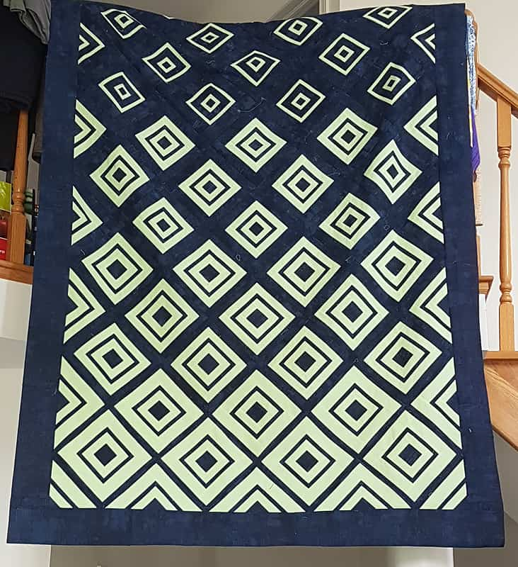 Julia's beautiful version of Bonjour Quilts' Diamonds in the Deep quilt pattern made in navy and white with a navy border.