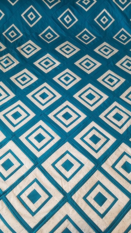 Pat's beautiful version of Bonjour Quilts' Diamonds in the Deep quilt pattern made with a low volume and teal fabric.