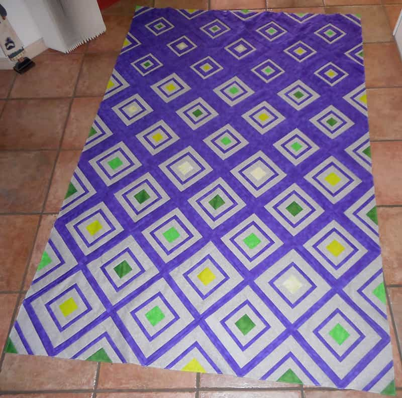 Cheryl's stunning version of Bonjour Quilts' Diamonds in the Deep quilt pattern made in purple and light grey, with coloured centre squares.