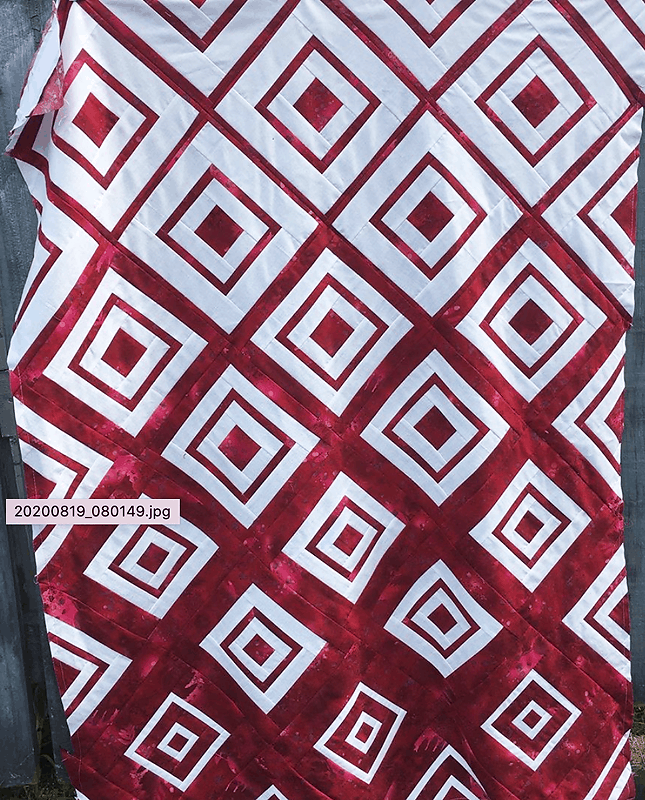 Kathy's beautiful version of Bonjour Quilts' Diamonds in the Deep quilt pattern made in red and white.