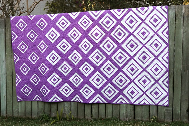 Purple and white Diamonds in the Deep quilt on a fence