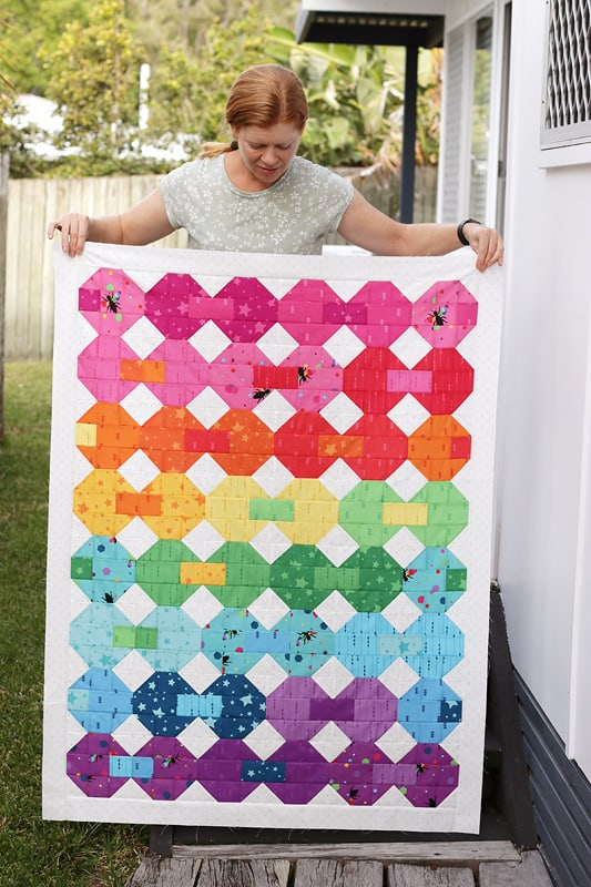 woman holding a quilt flimsy
