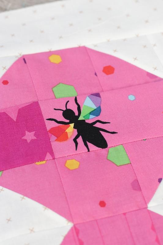 pink fabric with a printed bee in a quilt block